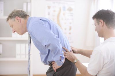 trainer helping man with lower back pain