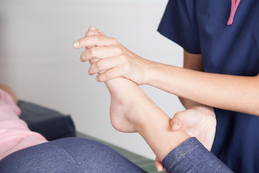 physical therapist helps patient relieve foot pain